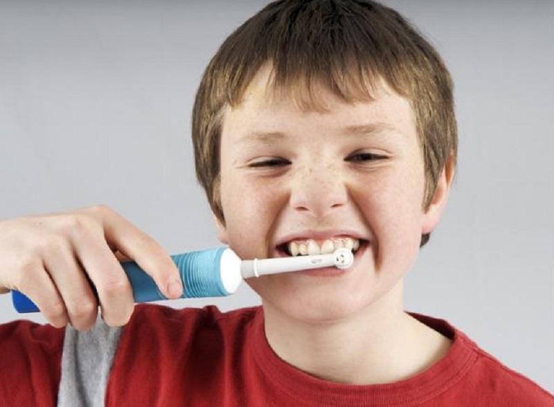Bambini che si lavano i enti con spazzolino elettrico