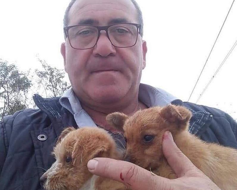 il macchinista con i due cuccioli di cane salvati